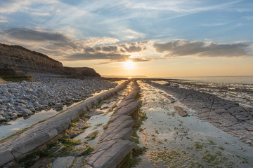 Setting Sun at Kilve Beach, Somerset, with Limestone (Blue Lias) wave cut platform, with rock pools