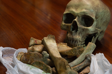 Old skull and bones in white bag on brown wooden table, still life image and space for texts