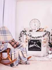 Xmas Fireplace with armchair, clocks and pillows. Christmas stocking over fireplace, New Year's card scenery. Snowman and stars. New Year concept.