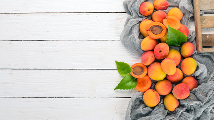 Fresh apricots with leaves On a white wooden background. Top view. Free space for your text.