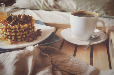 Cup of coffee and waffles with caramelized bananas, honey and walnuts on wooden tray. Morning breakfast in bed