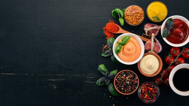 Set the sauces on a black wooden background. Ketchup, mayonnaise, mustard, soy sauce, barbecue sauce, pepper and spices. Top view. Free space for text.