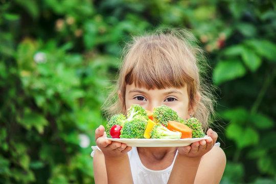 child eats vegetables. Summer photo. Selective focus.