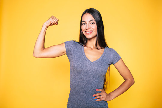 Sport, healthy lifestyle, gym, good body condition, women health, fitness concepts. Close up Portrait of Young cute sporty smiling brunette woman while she shows her arms and biceps on camera