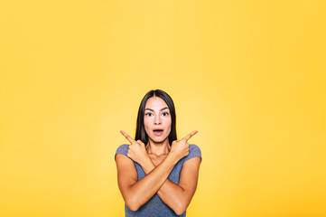Photo of young excited beautiful happy brunette woman, girl pointing away and smile isolated on yellow background banner Wall mural
