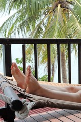 A Caucasian women lying on a hammock (close up shot of her legs) in Koh Samui, Thailand. This image can be used to represent the concept of being on holiday or vacation.