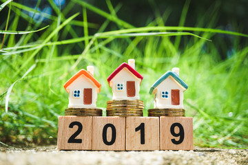 Miniature colorful house on golden stack coins and year 2019 wooden block using as business, family and property concept