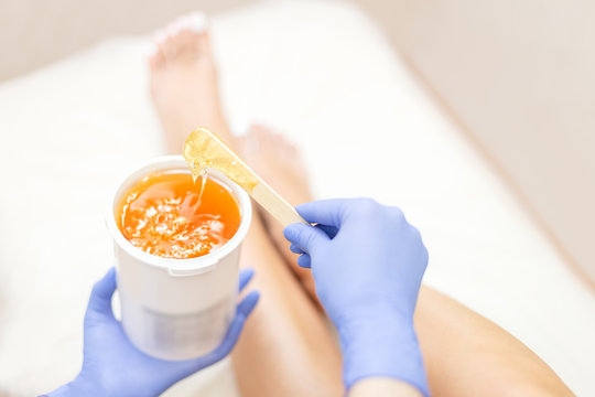 Close-up hands of cosmetologist in blue gloves holding paste for sugaring depilation