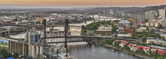 Drone aerial looking over an industrial area towards downtown Portland Oregon at sunrise