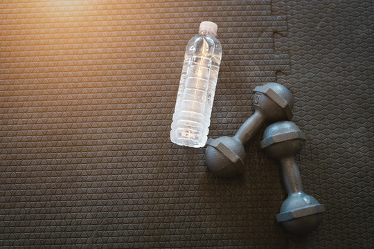 Dumbbells and water on a empty black rubber floor floor in defocused sport gym interior and fitness health club with sports exercise equipment,weight training equipment.
