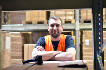 Portrait lächelnder Lagerist im Warenlager einer Spedition im Transportwesen // smiling worker in the warehouse of a freight forwarder