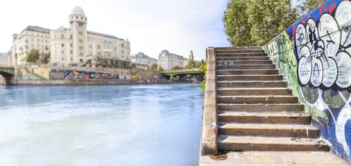 Fluss in Stadt. Stadtlandschaft mit Treppen neben Fluss. River in city center. Cityscape with stairs near river.