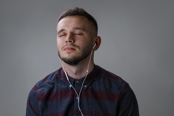 Lively guy listening music, closed eyes enjoy and relax over gray background