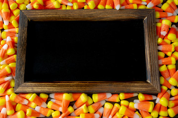 Halloween themed black board frame surrounded by candy corn.