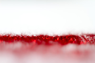 Red glitter texture on white background. Defocused.