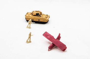 Miniature toy soldiers with a tank and a broken toy plane