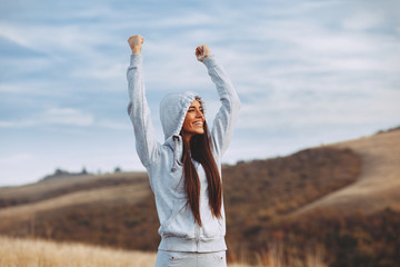 Young sport woman with raised arms motivates herself in nature