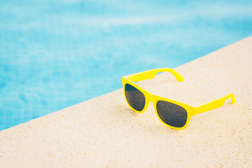 Yellow sunglasses near the blue pool