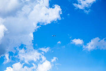 Cloudscape against a blue sky. The plane flies high above large white clouds. Travel on vacation with airlines.