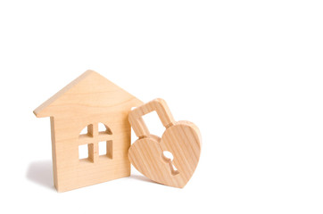 Wooden house with Heart shaped lock on a white background. Love nest, relationships. Buying a house with a young family. Affordable housing. Family psychology, strong relations. Love and offspring