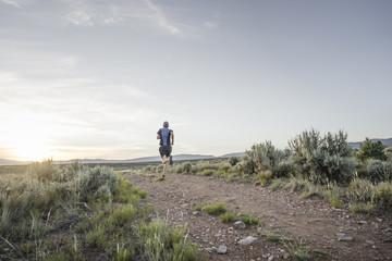 Man trail running through sagebrush desert, Taos, New Mexico, USA
