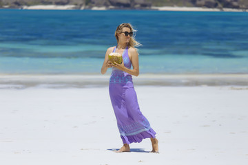 Woman with coconut drink on beach, Kuta, Lombok, Indonesia