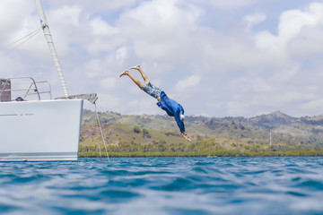Man diving in water from boat, Lombok, Indonesia