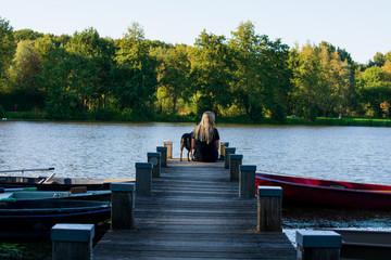 Junges Mädchen und ihr Hund sitzen gemeinsam auf einen Bootssteg und schauen einheitlich auf das Wasser. Standort: Deutschland, Nordrhein Westfalen