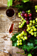 Wine background. Red wine in glasses, bottle, grapes on vintage background, wine concept. Copy space, top view flat lay background.