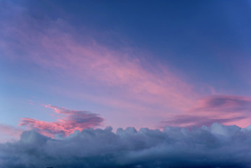 Dramatic sunset with clouds and pink orange blue sky