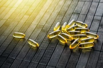 Golden Sunscreen pills on black wooden background in sunlight. Dietary supplements protect skin from the sun. Take pill and avoid the burn