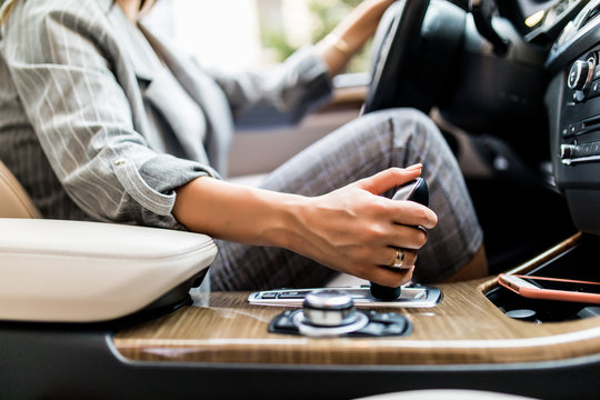 Business woman hand using a car automatic gear. Woman driving concept