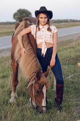 girl in cowboy black hat shirt jeans with horse
