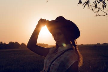 A silhouette of a cowgirl on sunset wildwest