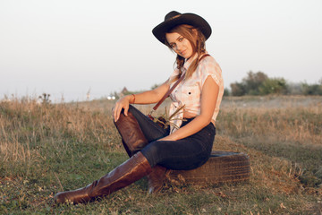 Girl cowgirl in jeans boots shirt and with a bag in a box with a wheel by a tree