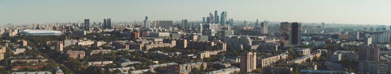 Panorama of evening summer cityscape with the residential district and dwelling houses in the foreground, multiple office skyscrapers and business high-rises in the distance; huge stadium on the left