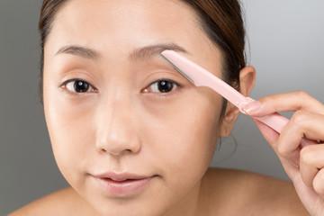 眉を剃る女性