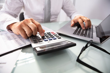 Businessman Using Laptop And Calculator