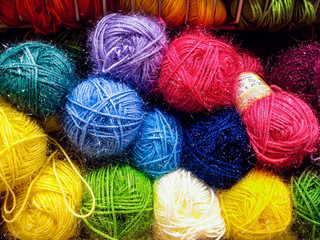 Many colorful yarn skeins on shelf in a handicraft shop