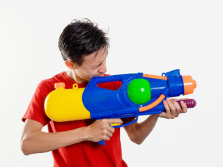 Young man with water gun toy Thailand Songkran Festival. Asian one person wear red short sleeves. isolated.