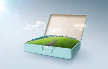 City skyline, green field, mountain and curvy asphalt highway in an open retro vintage suitcase isolated on light blue background .