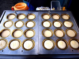 Mini pancakes being cooked on a food cart