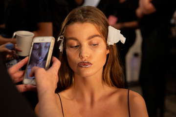 A make-up artist photographs a model backstage before the Jeremy Scott Spring/Summer 2019 collection during New York Fashion Week in the Manhattan borough of New York City