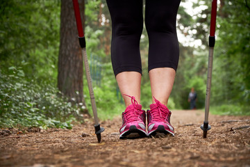 Close-up. Active mature lifestyle. Senior woman nordic walking in a countryside park.  Lifestyle concept