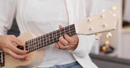 Woman practicing ukulele