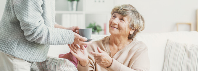 Close-up of person with cup of tea taking care of smiling senior woman