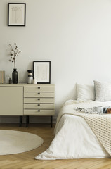 A monochromatic beige and white bedroom interior with a view at a bed and a drawer cabinet standing on a wooden floor. Real photo.