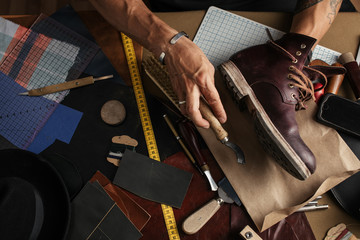 Shoe or belt maker working place at leather workshop with cobbler s and craft tools on background