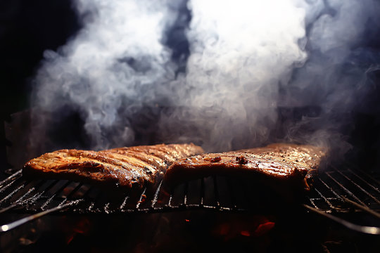 pork ribs on the grill cooking coals / fresh meat pork cooked on charcoal, summer home cooked meal, grilled ribs