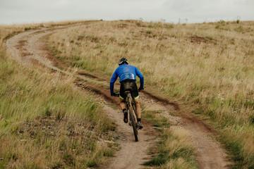 back male cyclist climbing uphill on mountain bike trail